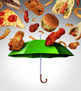 Bad diet protection food concept with a group of greasy fatty fast food falling down like rain and a green umbrella stopping the Stock Images