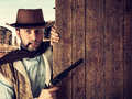 Bad gunman indicates with the gun a wooden plank in old wild west Stock Photography