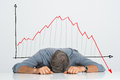 Bad investment depressed businessman leaning his head below a stock market chart Royalty Free Stock Image