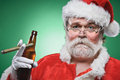 Bad santa with a beer and cigar smoking drinking Stock Photo