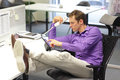 Bad sitting posture man in office young businessman caucasian his on phone working with tablet Stock Images