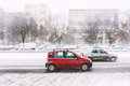 Bad winter weather driving cars speeding on road during heavy snowfall Stock Photo