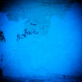 Badly damaged blue plaster wall background dark wallpaper Stock Photos