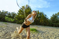Badminton motion in a game with blond girl on sand beach Royalty Free Stock Images