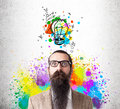 Baffled man in rainbow with colorful light bulb Royalty Free Stock Photo