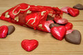 Bag of heart shaped chocolates a red full sweetheart spilling out onto a wooden table Royalty Free Stock Photography