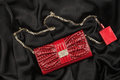 Bag of lacquered leather and red perfume lying on black silk. Handbag for women and bottle of scent, top view. Royalty Free Stock Photo