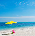 Bag parasol and sea yellow beach umbrella pink under a blue sky Royalty Free Stock Images