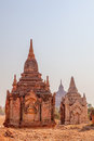 Bagan red and white pagoda in the field small stupa near bigger stupas myanmar Royalty Free Stock Photography