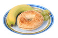 Bagel breakfast with banana on a plate Royalty Free Stock Photos