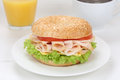 Bagel sandwich for breakfast with ham orange juice and coffee cream cheese tomatoes lettuce Stock Photos