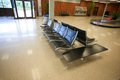 Baggage claim empty seats and luggage belt at an airport Royalty Free Stock Image