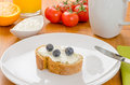 Baguette with cream cheese and blueberries on a table breakfast Stock Image