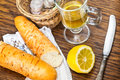 Baguette and tea with lemon for breakfast on a wooden table Royalty Free Stock Image