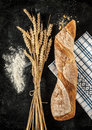 Baguette wheat and flour on black background bread roll or french chalkboard rural kitchen or bakery Royalty Free Stock Images
