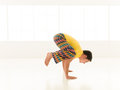 Bakasana side view colorful dressed male repeating yoga exercises in a white room with window background Stock Image