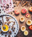 Baked apples with nuts and honey on a round baking sheet on a wooden background, around are lined with ingredients, nuts and Royalty Free Stock Photo