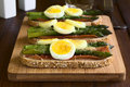 Baked asparagus ham egg and cheese sandwich green hard boiled grated warm on wooden board photographed on dark wood with natural Royalty Free Stock Photography