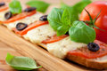 Baked baguette with mozzarella and tomatoes Royalty Free Stock Images