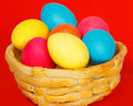 Baked basket with easter colored eggs on a red background Royalty Free Stock Image