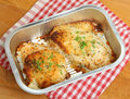 Baked chicken breast convenience meal two breasts with cheese and herbs in foil tray Stock Images