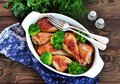 Baked chicken drumstick with organic broccoli on a wooden background. Royalty Free Stock Photo
