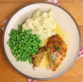 Baked chicken kiev breast with vegetables meal mashed potato and peas Stock Images