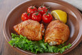 Baked chicken thigh with cherry tomatoes and lemon Stock Photo