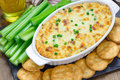 Baked crab dip served with celery sticks crackers and Stock Photos