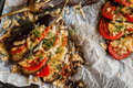 Baked eggplant in a fan shape on a baking sheet, top view. Cooked with tomatoes and cheese Royalty Free Stock Photo