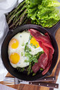 Baked eggs with asparagus and bacon Royalty Free Stock Photo