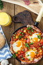 Baked eggs with chorizo, potatoes and tomatoes in a pan on the table. top view Royalty Free Stock Photo