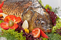 Baked fish decorated with vegetables and prepared for the banquet Stock Photos