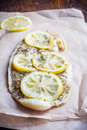 Baked fish with lemon and spices on a baking paper Royalty Free Stock Image