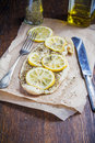 Baked fish with lemon and spices on a baking paper Royalty Free Stock Photos