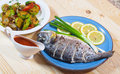 Baked fish on plate with lemons, and green onion Stock Photo