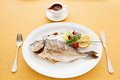 Baked fish with sauce and lemon Stock Image