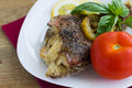 Baked grouper served with lemon and basil on white plate tomato Royalty Free Stock Photo