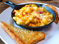 Baked mac and cheese in skillet fancy restaurant serves a hot with a side of texas toast Royalty Free Stock Images