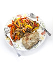 Baked meat with vegetables fork and spoon on white plate Royalty Free Stock Photo