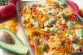 Baked nacho dish in a glass baking pan with corn tortilla chip, pico de gallo salsa, avocado guacamole chipotle, beans, jalapenos Royalty Free Stock Photo