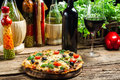 Baked pizza served with wine on the background of fresh vegetabl vegetables old wooden table Stock Photo