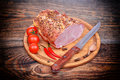 Baked pork neck tomatoes peppers garlic and knife Royalty Free Stock Photo