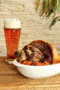 Baked pork shank with sauerkraut and beer on a wooden table Stock Image