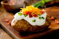 Baked potato closeup of a hot topped with sour cream bacon green onions and cheddar cheese Royalty Free Stock Photography