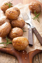 Baked potatoes on chopping board Royalty Free Stock Photos