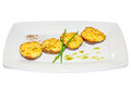 Baked potatoes with greens and spices on plate Stock Images
