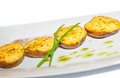 Baked potatoes with greens and spices on plate Royalty Free Stock Photos