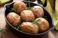 Baked potatoes with rosemary in black pan a Stock Image