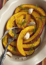 Baked pumpkin slices with garlic in baking dish Stock Images